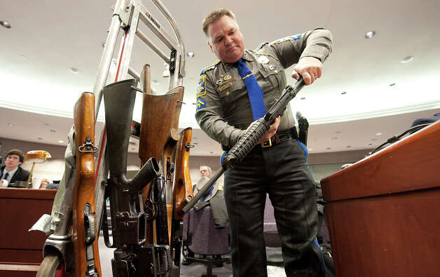 Connecticut State Trooper Joseph Delehanty unloads firearms for a demonstration during a hearing of a legislative subcommittee reviewing gun laws at the Legislative Office Building in Hartford, Conn., Monday, Jan. 28, 2013. The parents of children killed in the Newtown school shooting called for better enforcement of gun laws Monday at the legislative hearing. (AP Photo/Jessica Hill) Photo: Jessica Hill, ASSOCIATED PRESS / A2013