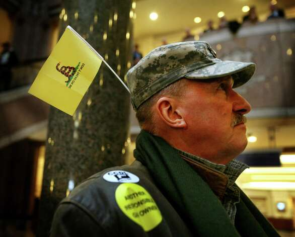 "Gun owner and Vietnam veteran George Rukstela, of Pomfret, wears a ""Don't Tread on Me"" flag on his hat to the Gun Violence Prevention Working Group hearing at the Legislative Office Building in Hartford on Monday, January 28, 2013. Photo: Brian A. Pounds / Connecticut Post"