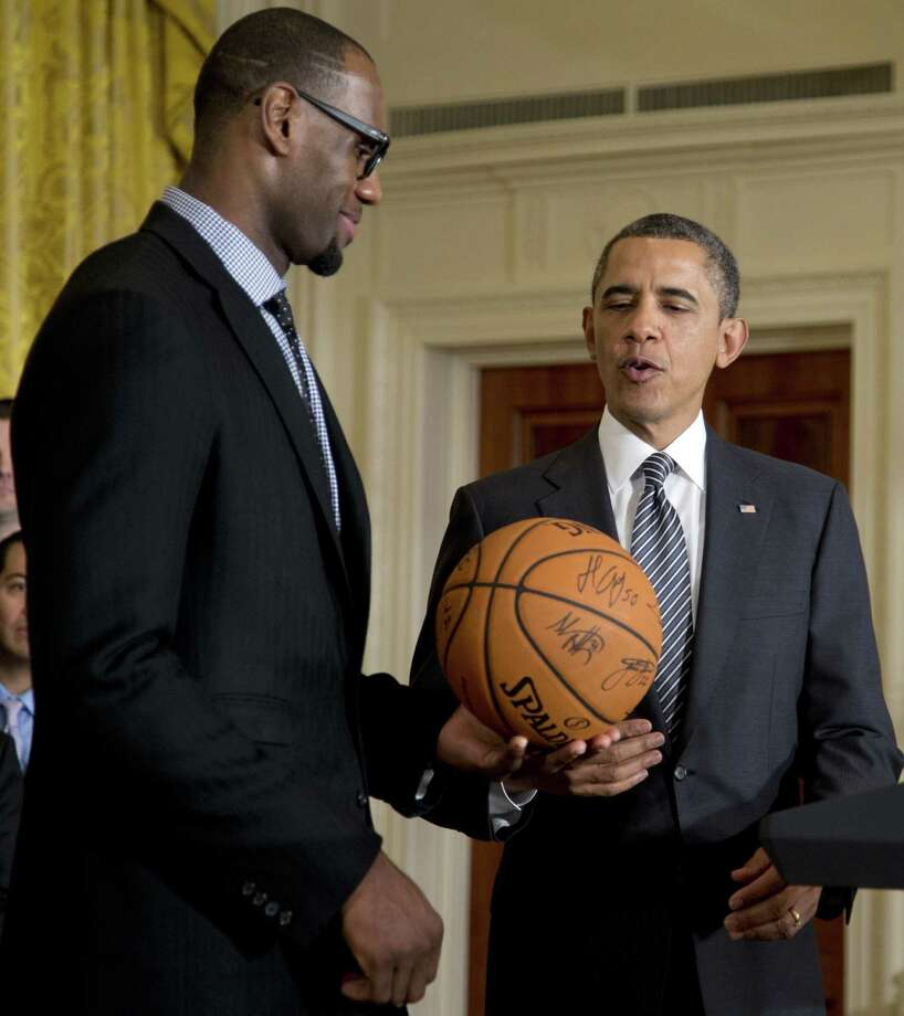 President Barack Obama accepts a signed basketball from Miami Heat forward LeBron James as he welcomes the the NBA basketball champion Miami Heat, to the East Room of the White House, Monday, Jan. 28, 2013, in Washington. (AP Photo/Carolyn Kaster) Photo: Carolyn Kaster