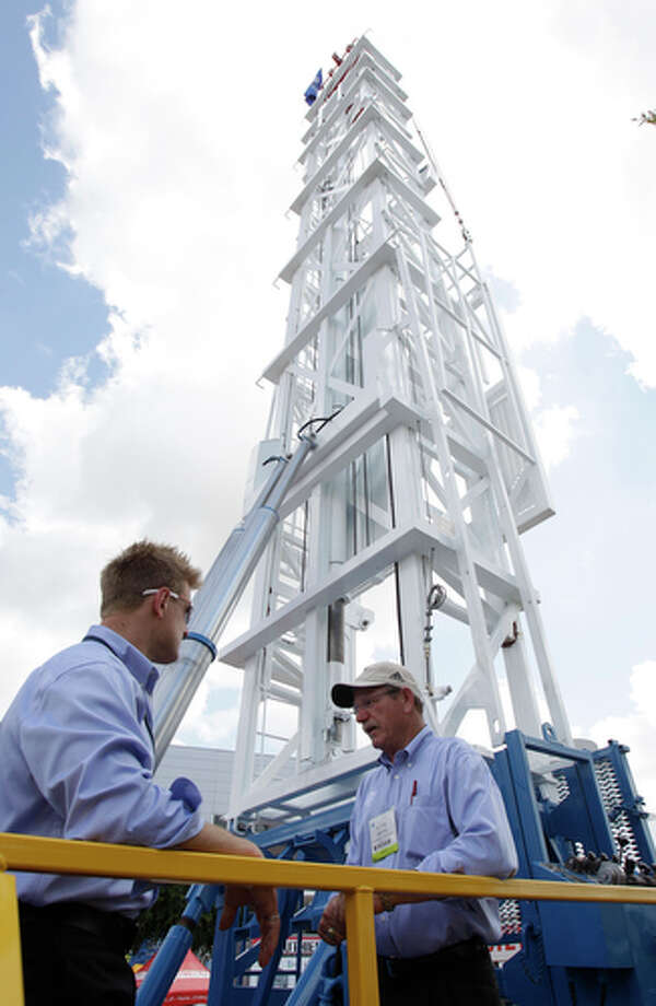 Rob Wawrzynowski, left, vice president of sales and marketing, and Floyd Blackie Smith, sales representative, with Stewart &Stevenson talk below the mast of a workover rig at their outdoor displays at OTC at Reliant Park Wednesday, May 2, 2012. Photo: Melissa Phillip, Houston Chronicle / © 2012 Houston Chronicle