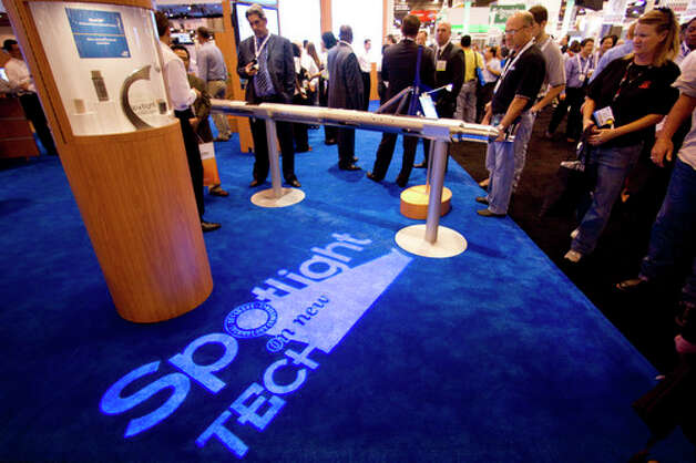 Attendees mill about the Baker Hughes booth during the 2012 Offshore Technology Conference Wednesday, May 2, 2012, in Houston. Photo: Brett Coomer, Houston Chronicle / © 2012 Houston Chronicle