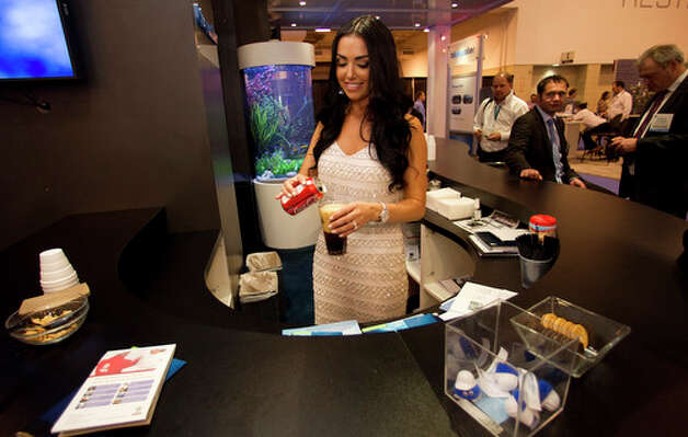 Magen Cheery pours a soda at the Bluewater booth during the 2012 Offshore Technology Conference Wednesday, May 2, 2012, in Houston. Photo: Brett Coomer, Houston Chronicle / © 2012 Houston Chronicle