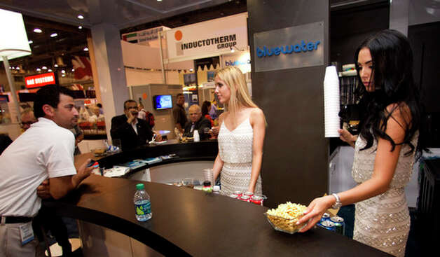 Molly Christian, center, and Magen Cherry serve beverages at the Bluewater booth during the 2012 Offshore Technology Conference Wednesday, May 2, 2012, in Houston. Photo: Brett Coomer, Houston Chronicle / © 2012 Houston Chronicle