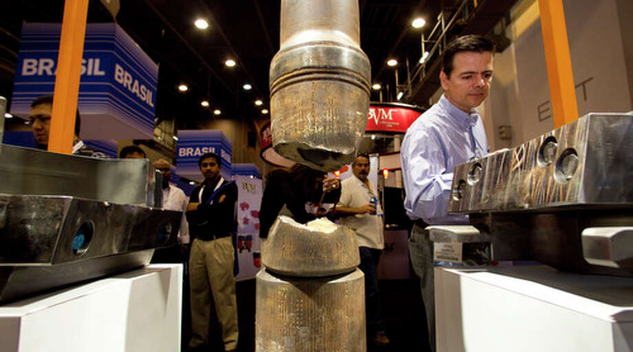 Jose Garcia, of Garcia & Mallitz, looks at a 5K Blind Shear Ram by GE during the 2012 Offshore Technology Conference Wednesday. Photo: Brett Coomer, Houston Chronicle / © 2012 Houston Chronicle