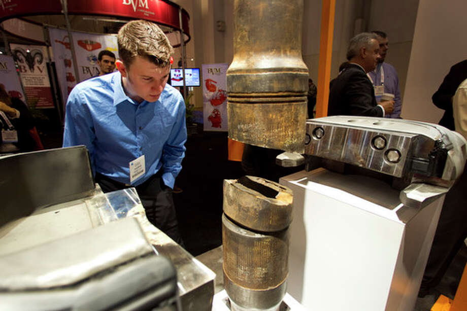 Cody Harris, of Baker Hughes, looks at a 5K Blind Shear Ram by GE during the 2012 Offshore Technology Conference Wednesday. Photo: Brett Coomer, Houston Chronicle / © 2012 Houston Chronicle