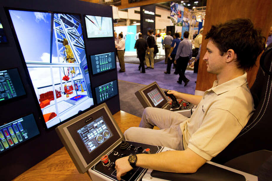 Julian Lang runs a drilling control system simulator by Jelec during the 2012 Offshore Technology Conference Wednesday, May 2, 2012, in Houston. Photo: Brett Coomer, Houston Chronicle / © 2012 Houston Chronicle