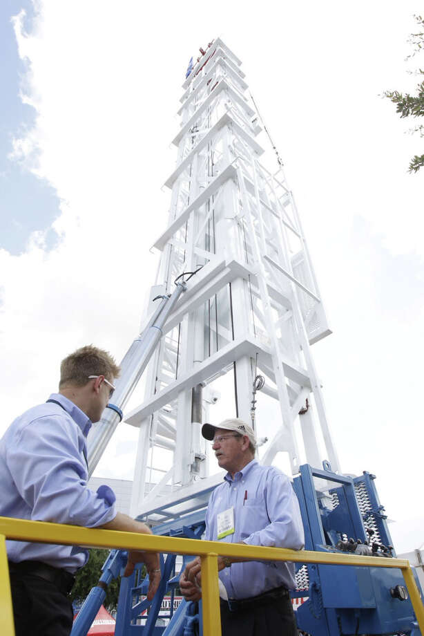 Rob Wawrzynowski and Floyd Smith with Stewart &Stevenson talk below the mast of a workover rig at their outdoor displays at OTC Wednesday.