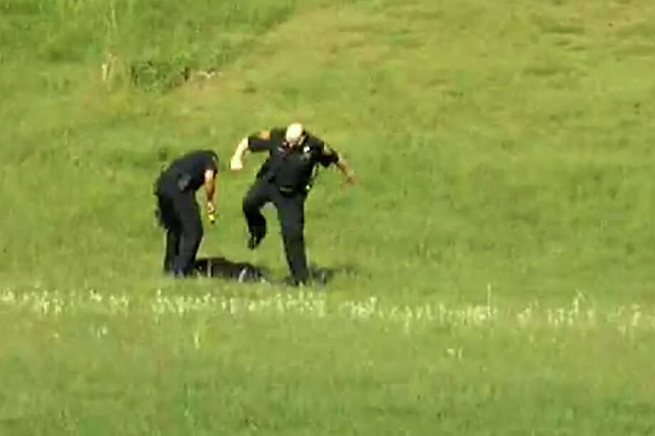 FILE — A screen grab from a video, posted on YouTube on Jan. 6, 2013, showing three Bridgeport, Conn. police officers kicking a man in Beardsley Park on May 20, 2011. Officers Elson Morales, Joseph Lawlor  and Clive Higgins were put on the paid administrative leave Jan.18, 2013 pending an investigation of the incident by the cityâÄôs Office of Internal Affairs. The man, who has not been identified, is lying on the ground after being Tasered by one of the officers when two of the officers begin kicking him. A third officer then gets out of his patrol car and walks over to where the other two are still kicking the man and then he too begins kicking him. Photo: Contributed Photo / Connecticut Post Contributed