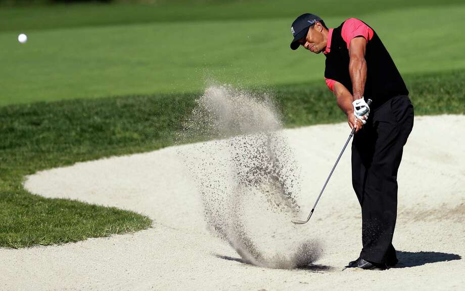 Tiger Woods hits out of a bunker on the 10th hole during the fourth round of the Farmers Insurance Open golf tournament at the Torrey Pines Golf Course, Monday, Jan. 28, 2013, in San Diego. (AP Photo/Gregory Bull) Photo: Gregory Bull, STF / AP