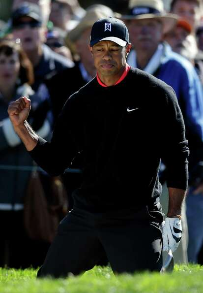 Tiger Woods raises a fist after hitting out of a bunker on the 11th hole during the fourth round of
