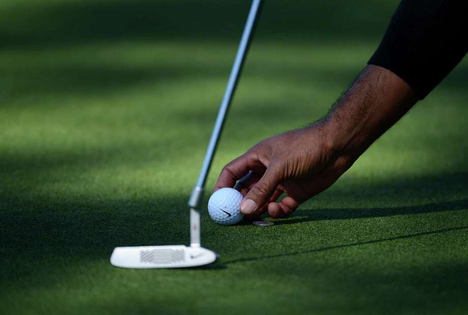 Tiger Woods places his ball on the 10th green during the Final Round at the Farmers Insurance Open. Photo: Donald Miralle, Getty Images / 2013 Getty Images