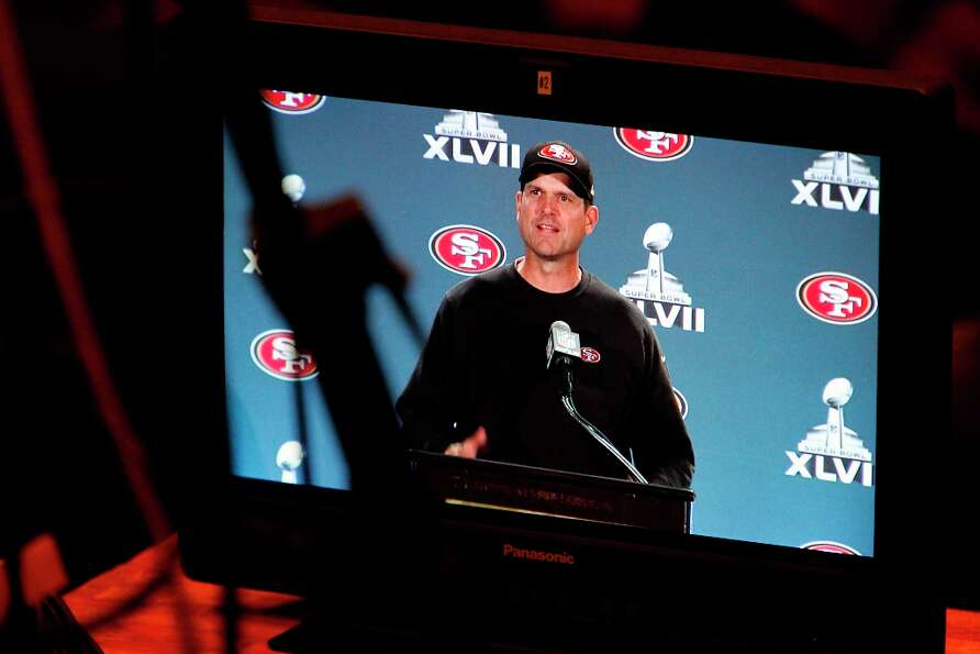 Head coach Jim Harbaugh as seen on a television monitor, speaks with reporters as the San Francisco