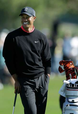 Tiger Woods smiles as he waits to putt on the 12th hole during the fourth round of the Farmers Insurance Open golf tournament at the Torrey Pines Golf Course Monday, Jan. 28, 2013, in San Diego. (AP Photo/Gregory Bull) Photo: Gregory Bull, Associated Press / AP