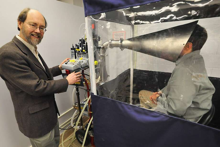 Professor Don Milton and a volunteer demonstrate the Gesundheit II machine, which analyzes how much flu virus a person expels. Photo: Amy Davis, McClatchy-Tribune News Service