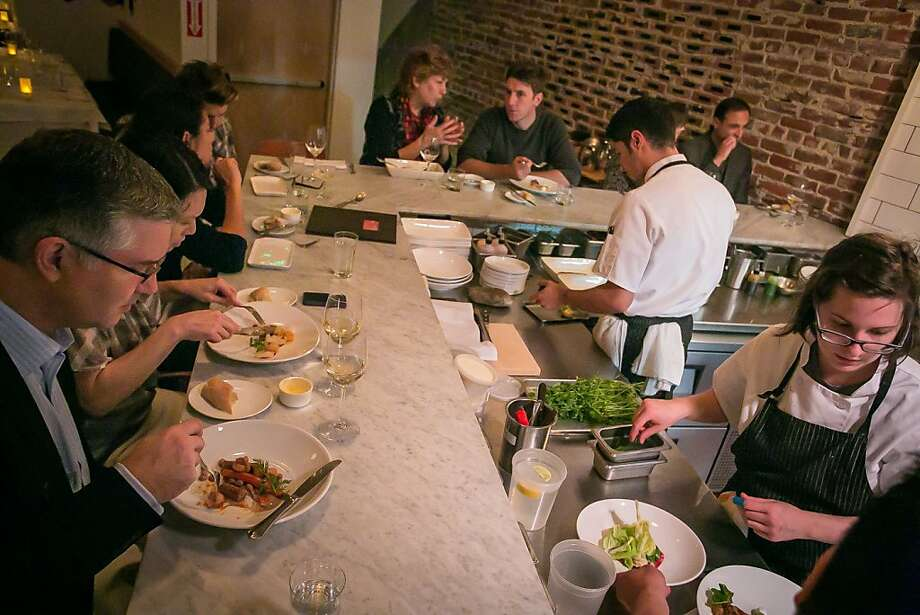 People watch food being prepared at the chef's counter at AQ. Photo: John Storey
