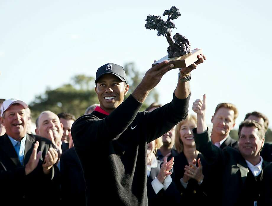 For the seventh time, Tiger Woods claims the trophy at the Torrey Pines event. Photo: Gregory Bull, Associated Press