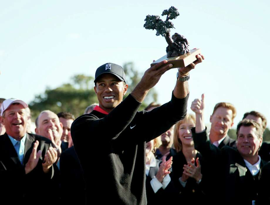 Tiger Woods holds up the trophy after winning the Farmers Insurance Open. Photo: Gregory Bull, Associated Press / AP