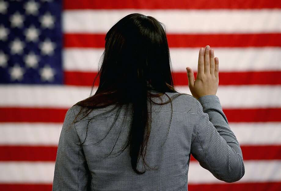 A woman takes the oath at a naturalization ceremony at the U.S. Citizenship and Immigration Services office in Newark, N.J. In 2012, 38,000 immigrants became citizens at that office. Photo: John Moore, Getty Images