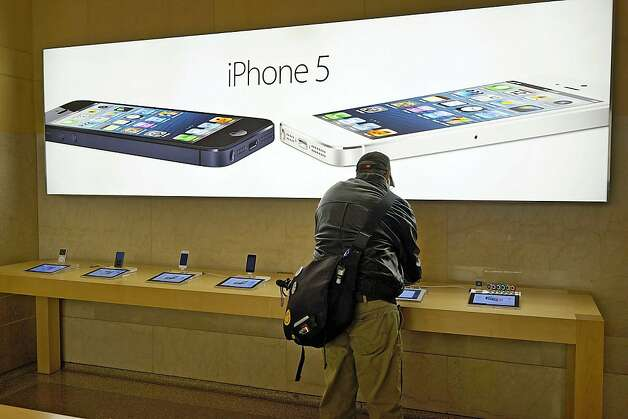 Advertisements for the iPhone 5 are displayed at an Apple store in New York City.  It is now once again illegal to unlock your cell phone in the USA. Photo: Spencer Platt, Getty Images