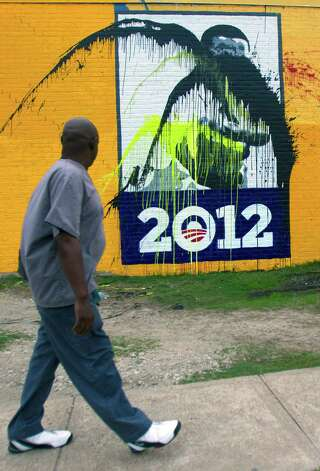 "Gregory Garner walks past a mural painted in honor of Obama after it was vandalized on Jan. 28. ""I just don't know what to say when people do that,"" said Garner. ""It's just terrible."" Photo: Cody Duty, Houston Chronicle / © 2013 Houston Chronicle"