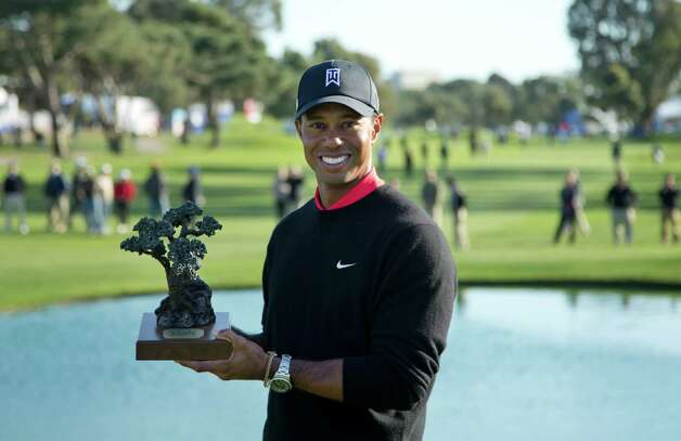 Tiger Woods holds up the trophy after winning the Farmers Insurance Open golf tournament at the Torrey Pines Golf Course Monday, Jan. 28, 2013, in San Diego. It is Wood's seventh victory in the event. (AP Photo/Gregory Bull) Photo: Gregory Bull, Associated Press / AP