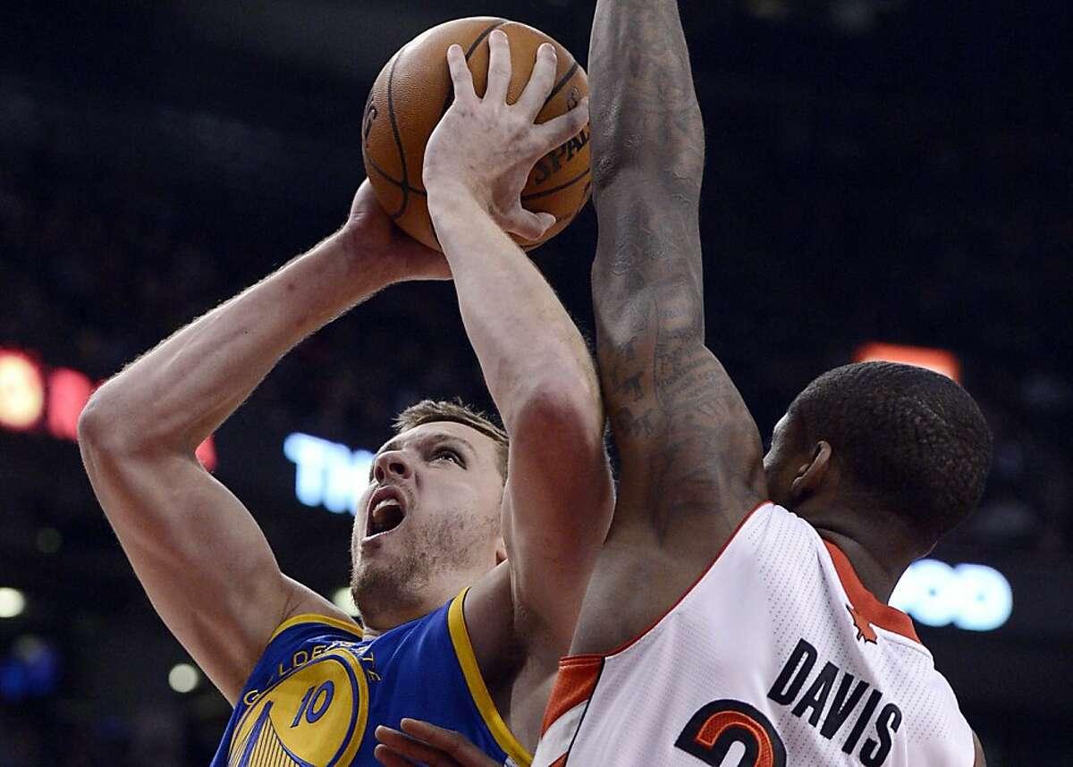 Golden State Warriors David Lee jumps past Toronto Raptors Ed Davis during NBA action in Toronto on Monday, Jan. 28, 2013. (AP Photo/The Canadian Press, Frank Gunn)