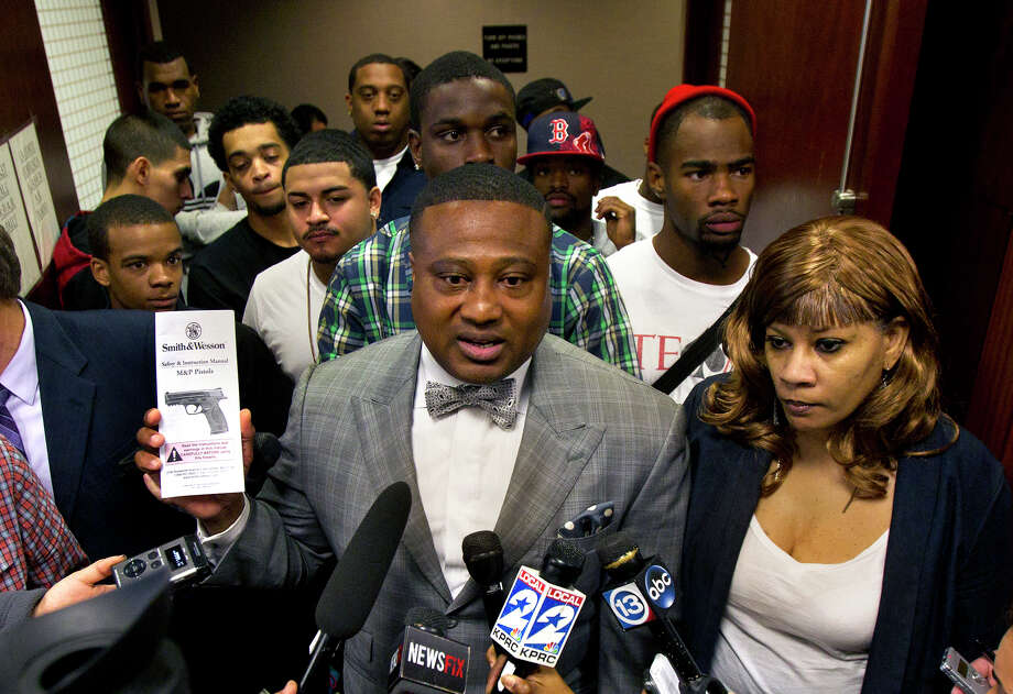 Quanell X - with Trey Foster's mother, Don - shows a receipt his client got when he bought a .40-caliber semiautomatic pistol. Photo: Cody Duty, Staff / © 2013 Houston Chronicle