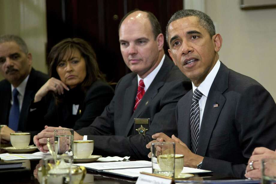 President Barack Obama meets with  representatives from Major Cities Chiefs Association and Major County Sheriffs Association in the Roosevelt Room of the White House, Monday, Jan. 28, 2013, in Washington, to discuss policies put forward by President Obama to reduce gun violence. From left are U.S. Attorney General Eric Holder, Minneapolis Police Chief Janee Harteau and Hennepin County Minnesota Sheriff Richard W. Stanek  (AP Photo/Carolyn Kaster) Photo: Carolyn Kaster
