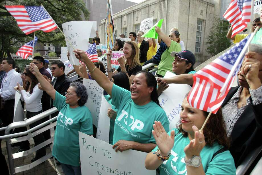 Members of the Texas Organizing Project Alicia Hernandez, center, and Karla Vargas, right, like what they hear as they join other local immigration reform advocates at an immigration reform news conference Monday at Houston City Hall. Photo: Melissa Phillip, Staff / © 2013 Houston Chronicle