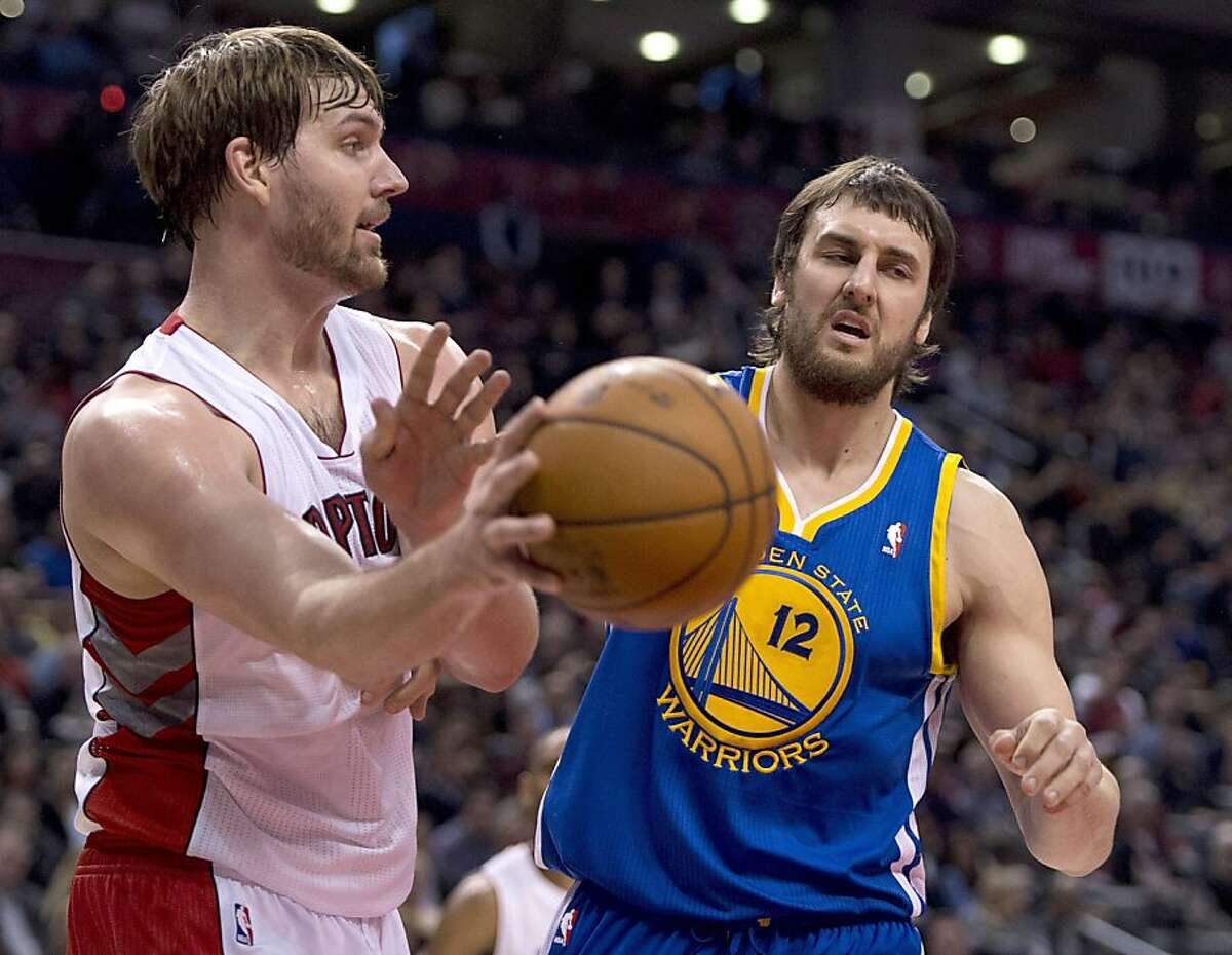 Golden State Warriors centre Andrew Bogut, right, guards Toronto Raptors center Aaron Gray, left, as he passes off the ball during first half NBA action in Toronto on Monday, Jan. 28, 2013. (AP Photo/The Canadian Press, Frank Gunn)
