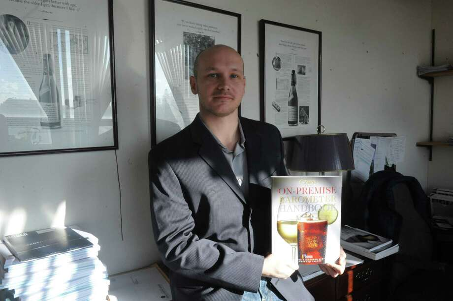 Adam Rogers holds the Cheers On-Premise BARometer Handbook that is sold to players it the liquor and beer and wine industry at his office in Norwalk, Wednesday, Jan. 23, 2013. It just came out and is done by The Beverage Information Group in Norwalk. Rogers is a senior research analyst. Photo: Helen Neafsey / Greenwich Time
