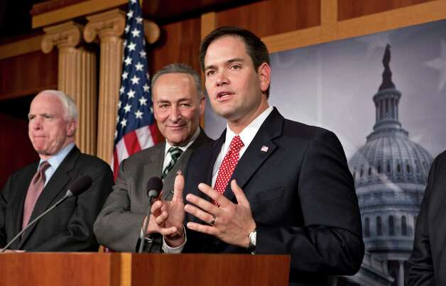 Sen. Marco Rubio, R-Fla., center, takes a reporter's question as a bipartisan group of leading senators announce that they have reached agreement on the principles of sweeping legislation to rewrite the nation's immigration laws, during a news conference at the Capitol in Washington, Monday, Jan. 28, 2013. From left are Sen. John McCain, R-Ariz., Sen. Charles Schumer, D-N.Y., and Sen. Marco Rubio, R-Fla. The deal covers border security, guest workers and employer verification, as well as a path to citizenship for the 11 million illegal immigrants already in this country.  (AP Photo/J. Scott Applewhite) Photo: J. Scott Applewhite
