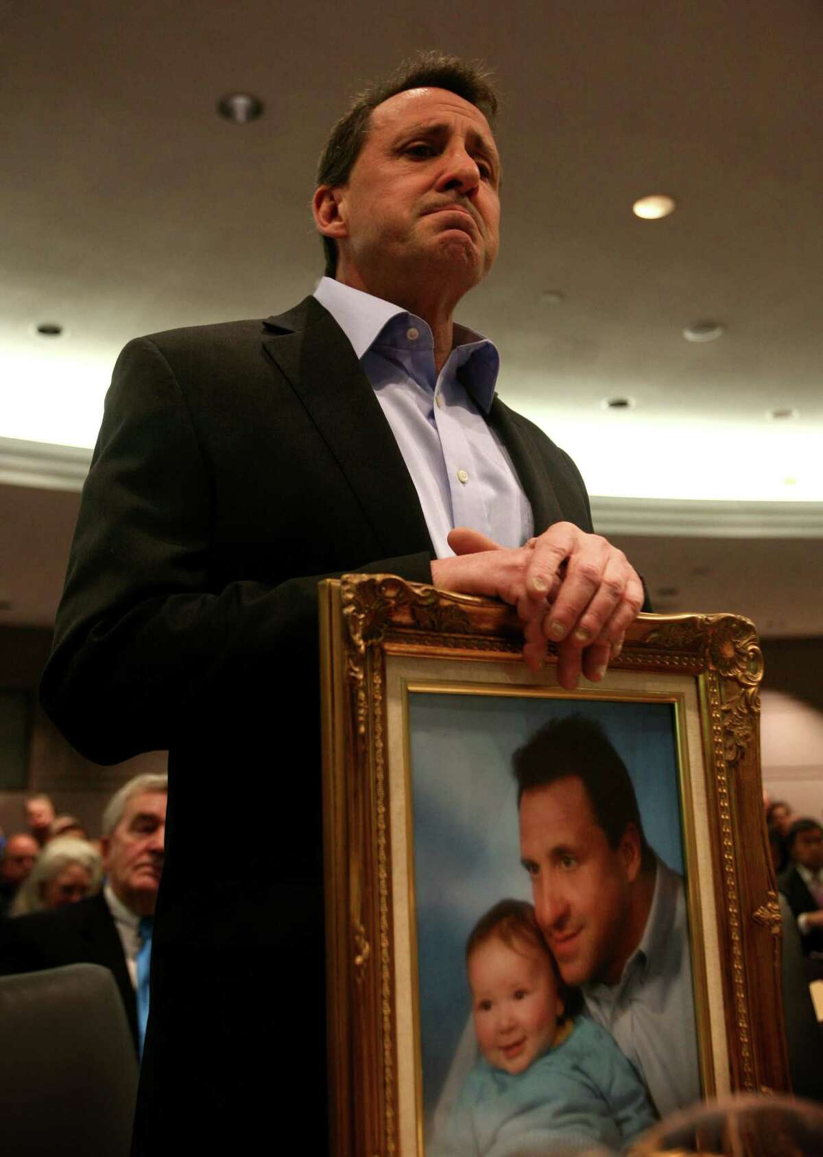Neil Heslin, of Shelton, holds a portrait of himself and his son, Jesse Lewis, one of the children killed in the Sandy Hook School shooting, during testimony before the Gun Violence Prevention Working Group at the Legislative Office Building in Hartford, Conn. on Monday, January 28, 2013.