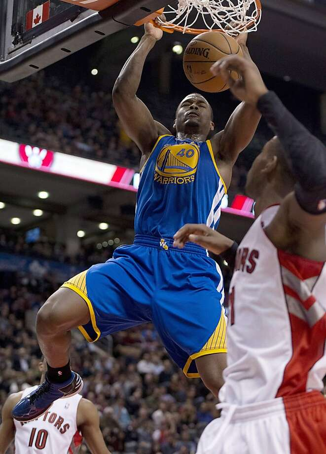 Golden State Warriors forward Harrison Barnes (40) slams home a dunk over Toronto Raptors forward Ed Davis, right, during second half NBA action in Toronto on Monday, Jan. 28, 2013. (AP Photo/The Canadian Press, Frank Gunn) Photo: Frank Gunn, Associated Press