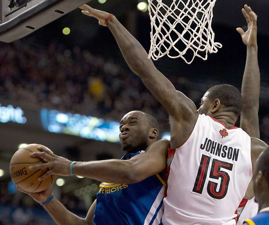Golden State Warriors forward Carl Landry, left, runs into stiff defense from Toronto Raptors forward Amir Johnson, right, during second half NBA action in Toronto on Monday, Jan. 28, 2013. (AP Photo/The Canadian Press, Frank Gunn) Photo: Frank Gunn, Associated Press
