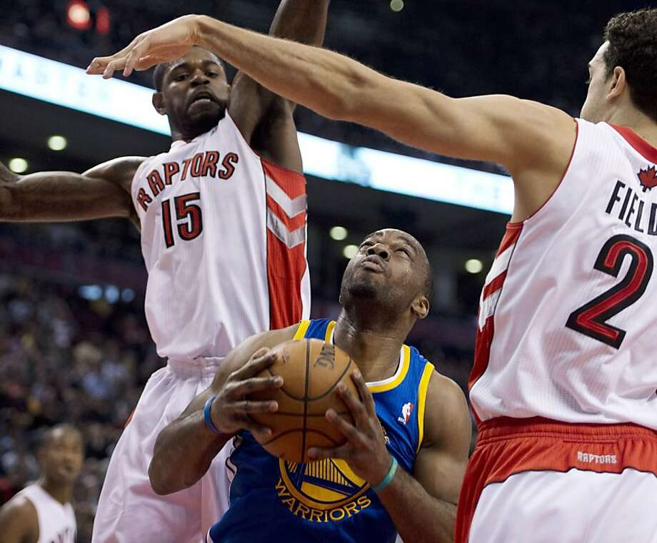 Golden State Warriors forward Carl Landry, bottom, tries to find a way to the basket past Toronto Raptors forward Amir Johnson (15) and Landry Fields (2) during the first half of their NBA basketball game, Monday, Jan. 28, 2013, in Toronto. (AP Photo/The Canadian Press, Frank Gunn) Photo: Frank Gunn, Associated Press