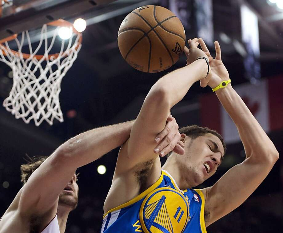 Golden State Warriors guard Klay Thompson (11) is fouled by Toronto Raptors center Aaron Gray during the first half of their NBA basketball game, Monday, Jan. 28, 2013, in Toronto. (AP Photo/The Canadian Press, Frank Gunn) Photo: Frank Gunn, Associated Press