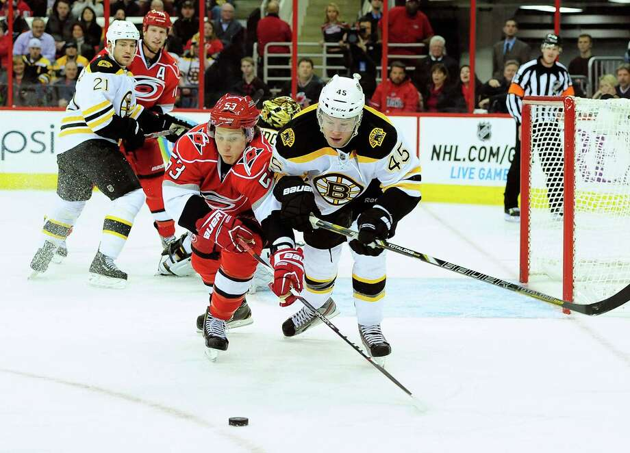 RALEIGH, NC - JANUARY 28:  Aaron Johnson #45 of the Boston Bruins battles for the puck with Jeff Skinner #53 of the Carolina Hurricanes during play at PNC Arena on January 28, 2013 in Raleigh, North Carolina.  (Photo by Grant Halverson/Getty Images) Photo: Grant Halverson