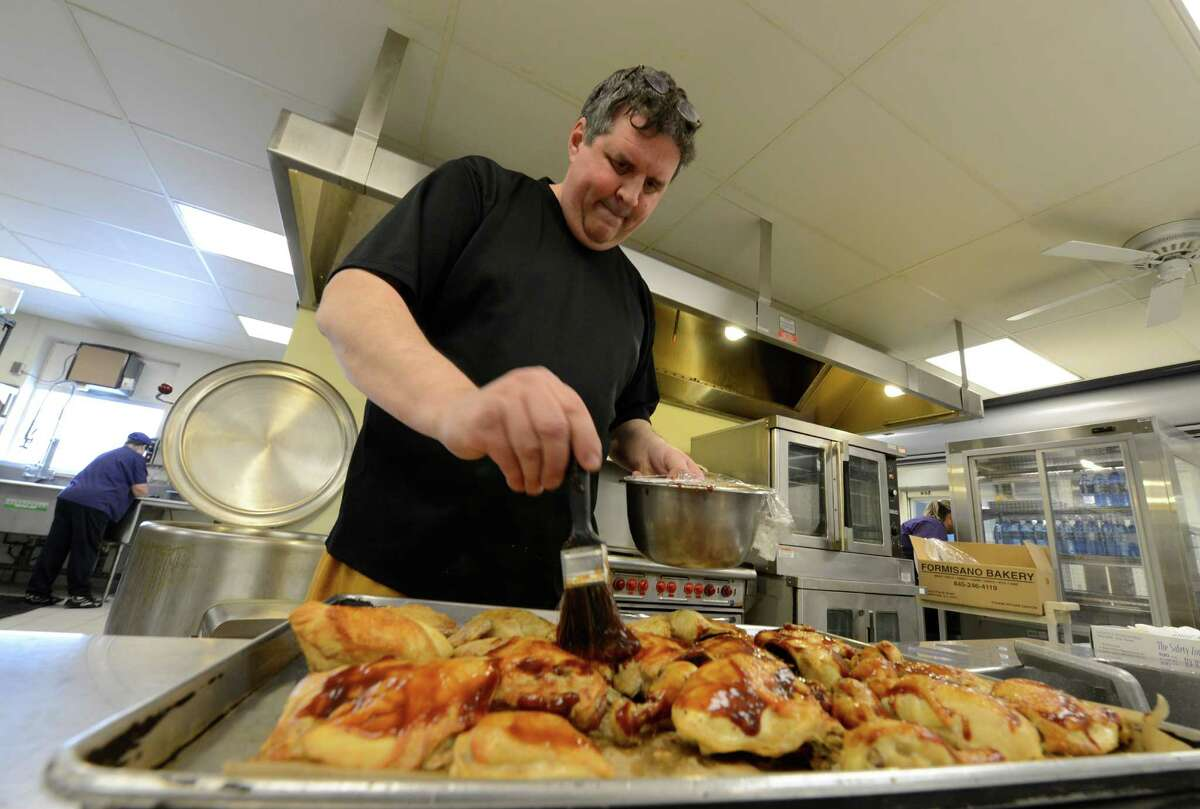 Culinary Institute-trained chef Tim Mulligan brushes some barbecue sauce on chicken breasts during the lunch recess Jan. 28, 2013 at the Voorheesville High School in Voorheesville, N.Y. (Skip Dickstein/Times Union)