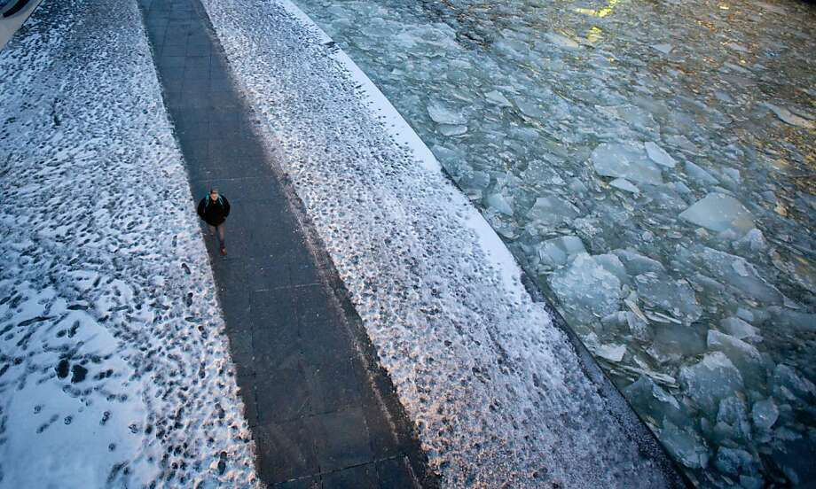 TOPSHOTS  A man walks past the Spree river covered with ice sheets on January 28, 2013 in Berlin. After some days of cold spell, temperatures in the German capital are rising again.       AFP PHOTO / KAY NIETFELD    GERMANY OUTKAY NIETFELD/AFP/Getty Images Photo: Kay Nietfeld, AFP/Getty Images
