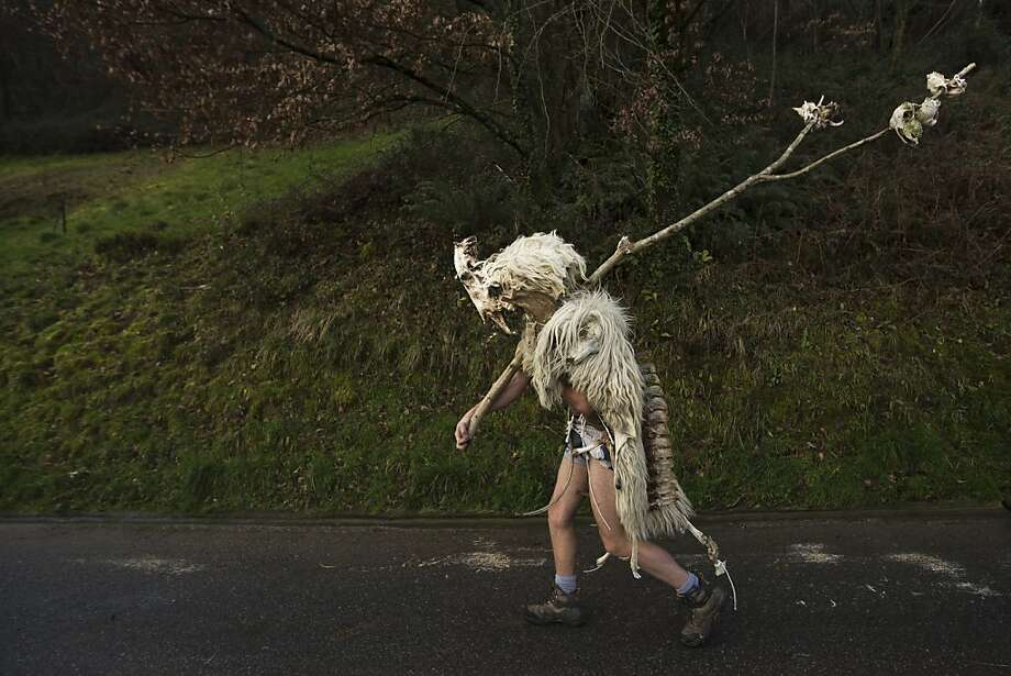 """Snort softly and carry a big stick:A man dressed as a Momotxorro - a half-human, half-bull entity wearing horns and sheepskin - walks to a carnival celebration in the Basque village of Zubieta, Spain. The pagan creatures, which date back to before the Roman Empire, traditionally run around the village threatening people with their """"forks."""" Photo: Daniel Ochoa De Olza, Associated Press"""