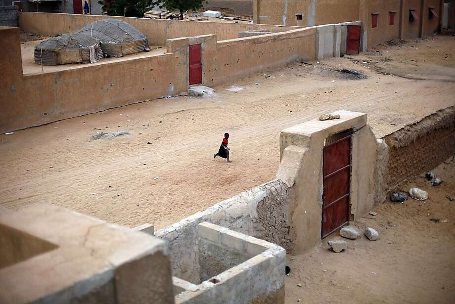 A young child runs through the deserted side streets of Gao , Northern Mali, Monday Jan. 28, 2013. French and Malian troops held a strategic bridge and the airport in the northern town of Gao on Sunday as their force also pressed toward Timbuktu, another stronghold of Islamic extremists in northern Mali, officials said. Malian soldiers descended on the city of Timbuktu on Monday after al-Qaida-linked militants fled into the desert having set ablaze a library that held thousands of ancient manuscripts.  (AP Photo/Jerome Delay) Photo: Jerome Delay, Associated Press