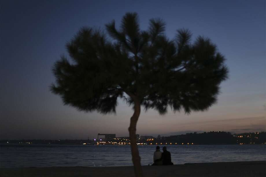 A couple sit by the Tagus river bank at sunset in Lisbon, Monday, Jan. 28, 2013. (AP Photo/Francisco Seco) Photo: Francisco Seco, Associated Press