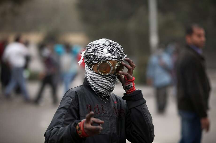 An Egyptian protester covers his face during clashes with riot police, not seen, near Tahrir Square, Cairo, Egypt, Monday, Jan. 28, 2013. Health and security officials say a protester has been killed in clashes between rock-throwing demonstrators and police near Tahrir Square in central Cairo. The officials say the protester died Monday on the way to the hospital after being shot. (AP Photo/Khalil Hamra) Photo: Khalil Hamra, Associated Press