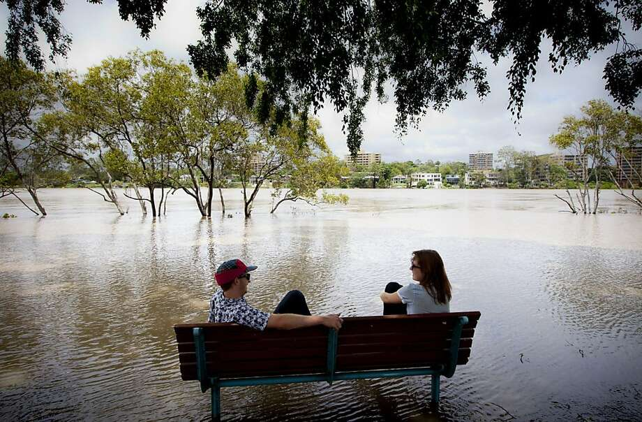 TOPSHOTS  Peter Wison (L) and Beata Jaremko sit on a bench surrounded by floodwaters as the Brisbane River brakes its banks at West End in Brisbane on January 28, 2013. Helicopters plucked dozens of stranded Australians to safety in dramatic rooftop rescues on January 28 as severe floods swept the northeast, killing three people and inundating thousands of homes.AFP PHOTO / Patrick HAMILTONPATRICK HAMILTON/AFP/Getty Images Photo: Patrick Hamilton, AFP/Getty Images