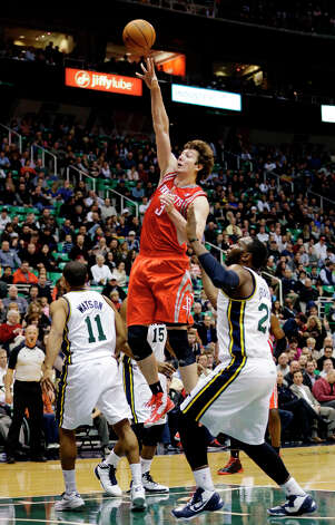 Rockets center Omer Asik shoots over Al Jefferson and Earl Watson of the Jazz. Photo: Rick Bowmer