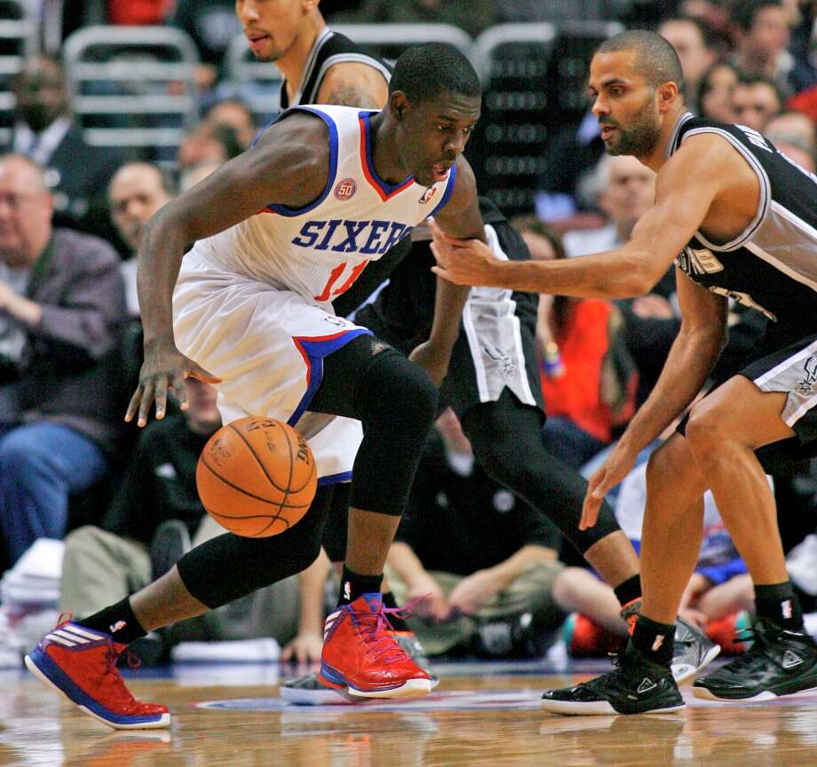 Philadelphia 76ers' Jrue Holiday (11) drives against the Spurs' Tony Parker during the first half Monday Jan. 21, 2013, in Philadelphia. Photo: H. Rumph Jr., Associated Press / FR61717 AP