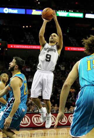 The Spurs' Tony Parker (09) takes a short jumper in the paint against New Orleans Hornets' Greivis Vasquez (21) in the second half on Wednesday, Jan. 23, 2013. Spurs defeated the Hornets, 106-102. Photo: Kin Man Hui, San Antonio Express-News / © 2012 San Antonio Express-News