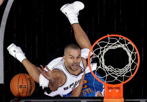 The Spurs' Tony Parker scores over New Orleans Hornets' Greivis Vasquez, obscured, during the first quarter, Wednesday, Jan. 23, 2013, in San Antonio. Photo: Eric Gay, Associated Press / AP