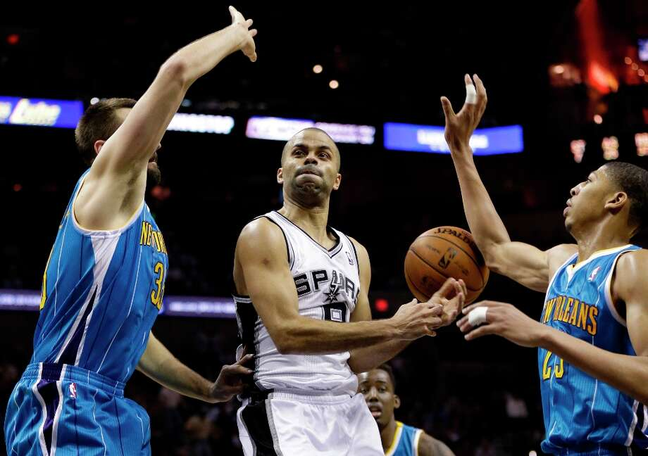 The Spurs' Tony Parker (center) loses control of the ball as New Orleans Hornets' Anthony Davis (right) and New Orleans Hornets' Ryan Anderson (left) defend during the fourth quarter, Wednesday, Jan. 23, 2013, in San Antonio. Photo: Eric Gay, Associated Press / AP